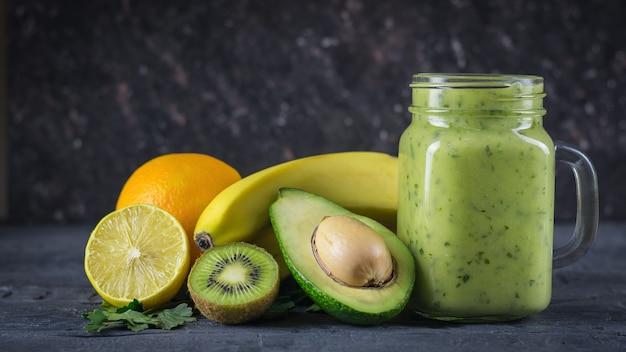 Smoothie von avocado, banane, kiwi und zitrone auf einem holztisch gegen eine schwarze wand vegetarisches essen für einen gesunden lebensstil