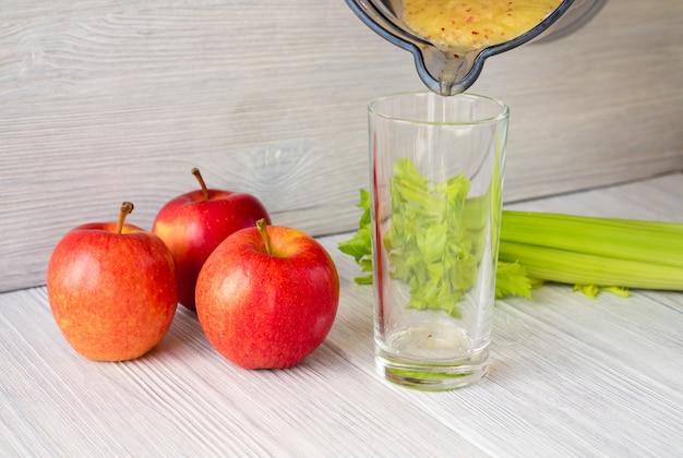 Smoothies aus äpfeln und sellerie in ein glas gegossen