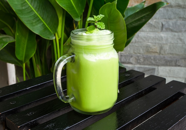 Smoothies des grünen tees im glas auf schwarzem holztisch.