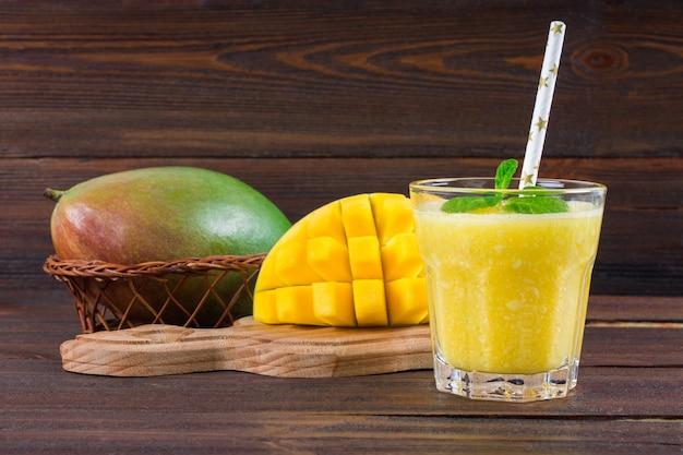 Smoothies mango mit stroh und minze in einem becherglas. platte mit geschnittener mango.