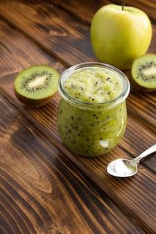 Smoothies oder püree mit kiwi und apfel im kleinen glas auf der braunen holzoberfläche. lage vertikal.