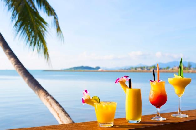 Smoothies und cocktail-mango-getränke mit stroh und minze in einem becherglas. eine tropische frucht. auf holzschreibtisch und tropischer kokosnuss