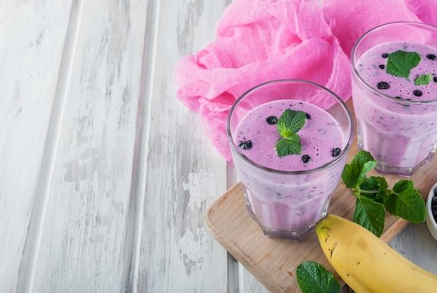 Smoothies von blaubeeren und banane in gläsern und zutaten auf einem holztisch