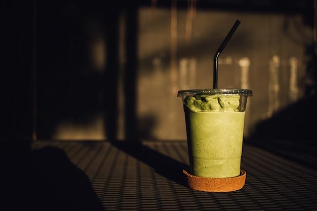 Smoothy milch aus grünem tee in einem plastikglas.