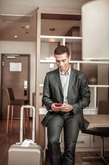 Sms frau. junger afroamerikanischer geschäftsmann, der seiner frau eine sms schreibt, nachdem er ins hotelzimmer gekommen ist