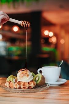 Snack auf einer waffel mit eis und obst, während mit karamellsirup belegt. speicherplatz kopieren