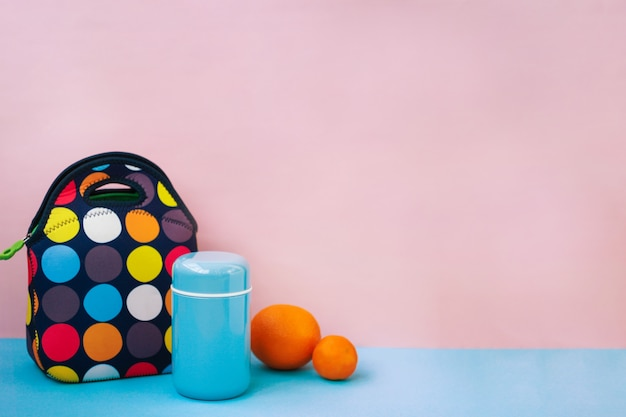 Snack für eine pause mit einer lunchbox. bunte handtasche, blaue thermoskanne, orange, mandarine. , rosa .