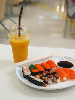 Snack im food court des einkaufszentrums. sushi-set auf einem teller.