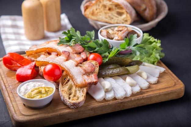 Snack mit gebratenem bruststück, brot, geschnittenem schmalz, frischen tomaten und marinierten pilzen. leckere vorspeise auf holzbrett