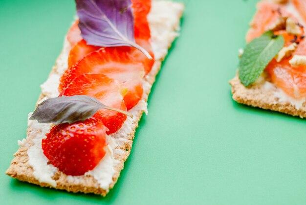 Snack mit knäckebrot, frischkäse, erdbeere und basilikum