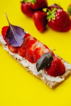 Snack mit knäckebrot, frischkäse, frischer erdbeere und basilikum auf gelbem grund