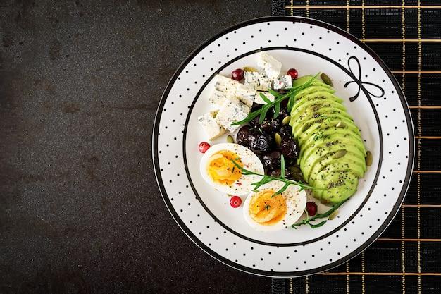 Snack oder gesundes frühstück - teller mit blauschimmelkäse, avocado, gekochtes ei, oliven auf einer schwarzen oberfläche. ansicht von oben