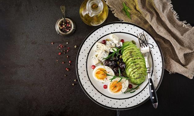 Snack oder gesundes frühstück - teller mit blauschimmelkäse, avocado, gekochtes ei, oliven