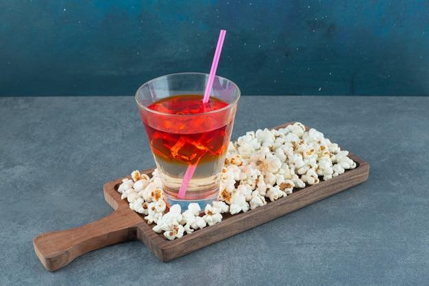 Snack-set aus popcorn-haufen und einem glas kaltem saft, serviert auf einem holzbrett auf blauem hintergrund. foto in hoher qualität