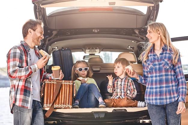 Snack-time-familie steht in der nähe des autos und macht einen familien-roadtrip zum mittagessen