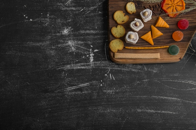 Snack und gebäckbrett auf schwarzem hintergrund