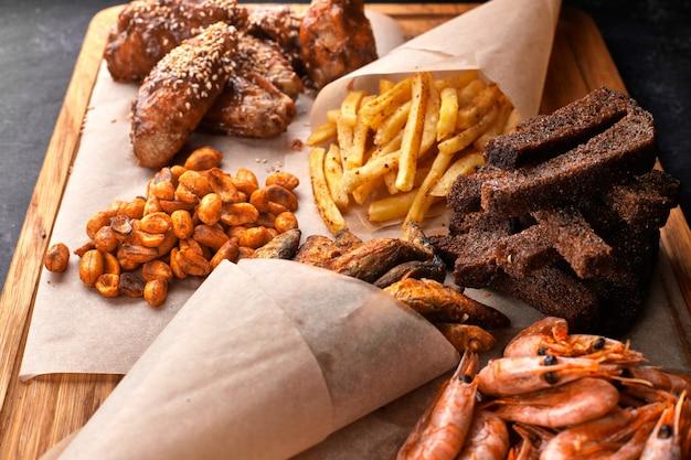 Snack zum bier auf einem holzbrett. garnele. gebratener fisch. gebratene erdnüsse. pommes. hühnerflügel. knirschen. croutons.