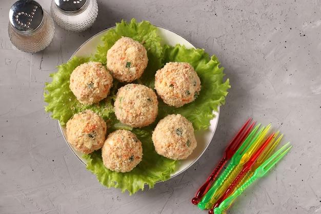 Snackbällchen mit hühnchen, karotten, käse und frühlingszwiebeln in crackerkrümeln, draufsicht auf grauen betontisch, blick von oben