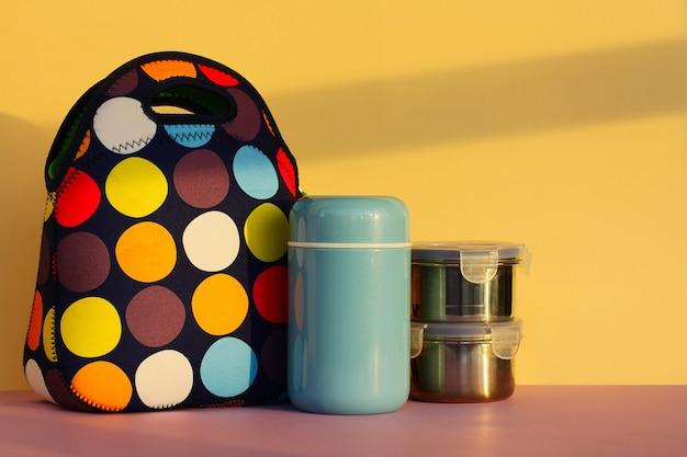 Snacken sie eine pause mit einer lunchbox. bunte handtasche, blaue thermoskanne und zwei metallbehälter mit essen. mittagessen für einen schüler oder einen büroangestellten. platz für text, gelber hintergrund