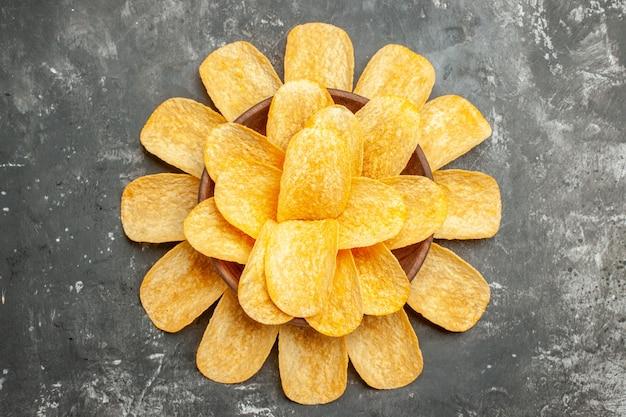 Snackparty für freunde mit köstlichen kartoffelchips auf grauem hintergrund