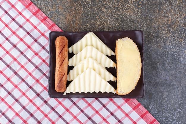 Snackplatte mit brotscheiben, wurst und käse