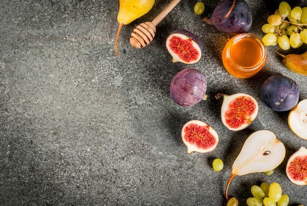 Snacks, diätetische vegane desserts. herbst trägt feigen, birnen, trauben mit honig auf einer schwarzen steintabelle früchte. copyspace draufsicht