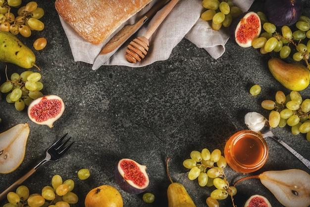Snacks, diätetische vegane desserts. herbstfrüchte (feigen, birnen, trauben) mit honig