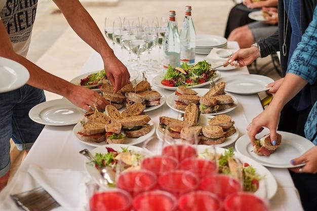 Snacks, fisch- und fleischspezialitäten am buffet. weißer tisch