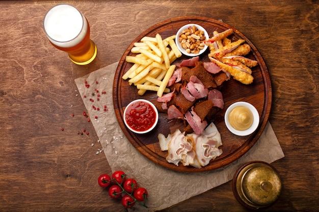 Snacks für bier oder alkohol. dazu gehören geräuchertes schweinefleisch, pommes frites, gebratenes brot, krabbenstäbchen und nüsse