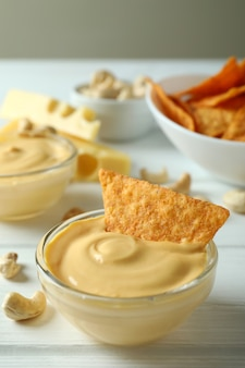 Snacks mit käsesauce auf weißem holztisch