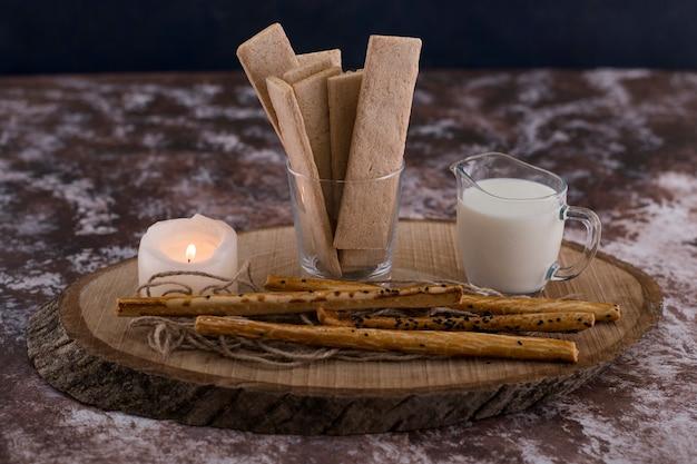 Snacks und cracker mit einem glas milch auf rustikal mit einer brennenden kerze.