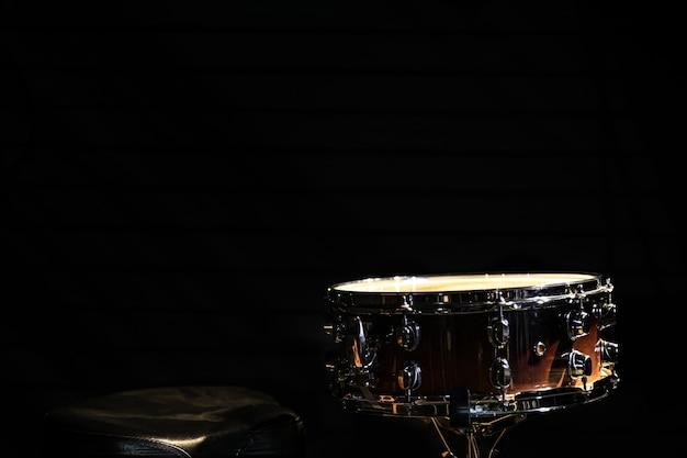 Snare drum auf schwarzem hintergrund, schlaginstrument im dunkeln, kopierraum.