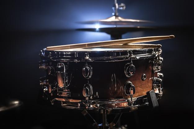 Snare drum, schlaginstrument auf dunklem hintergrund mit bühnenbeleuchtung.