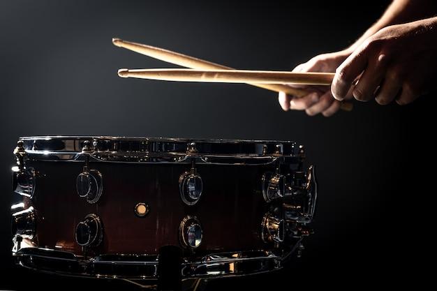 Snare drum und schlagzeugerhände schlagen drumsticks vor einem dunklen hintergrund.