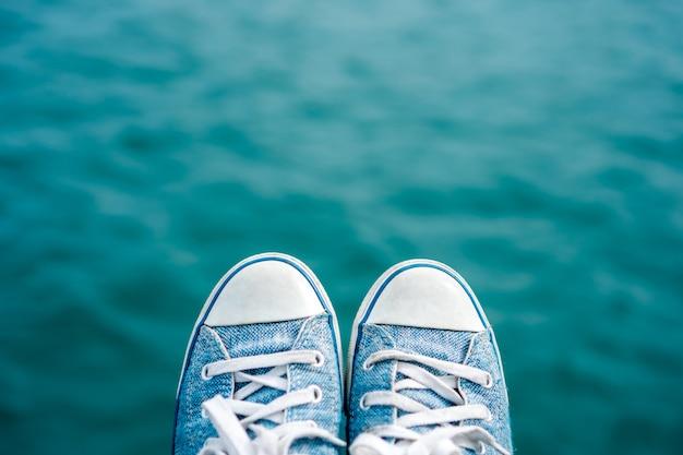 Sneaker schuh auf verschwommenem blauen ozean mit bokeh.