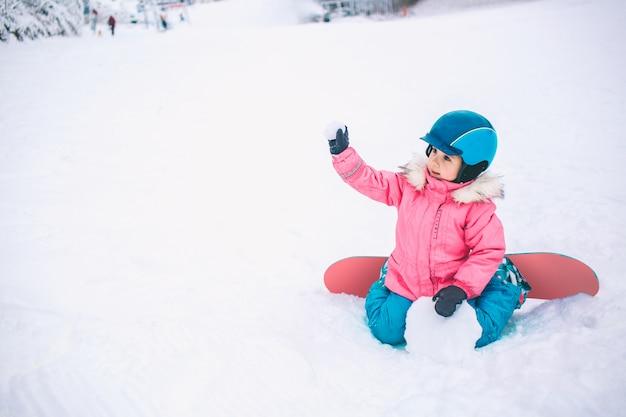 Snowboard wintersport. das kleinkindmädchen, das mit dem schnee trägt warme winterkleidung spielt. winter