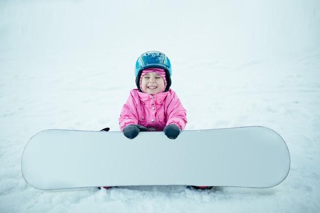 Snowboard wintersport. kleines kind, das mit schnee spielt, der warme winterkleidung trägt.