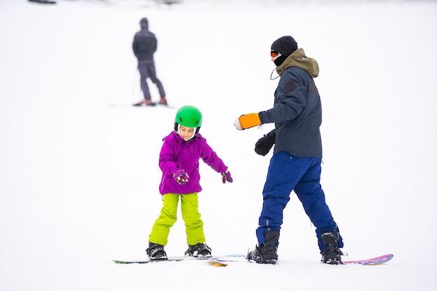 Snowboard-wintersport. kleines mädchen, das snowboarden lernt und warme winterkleidung trägt. winter-hintergrund.