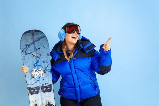 Snowboarden. porträt der kaukasischen frau auf blauem studiohintergrund. schönes weibliches modell in warmer kleidung. konzept der emotionen, gesichtsausdruck, verkauf, anzeige. winterstimmung, weihnachtszeit, feiertage.
