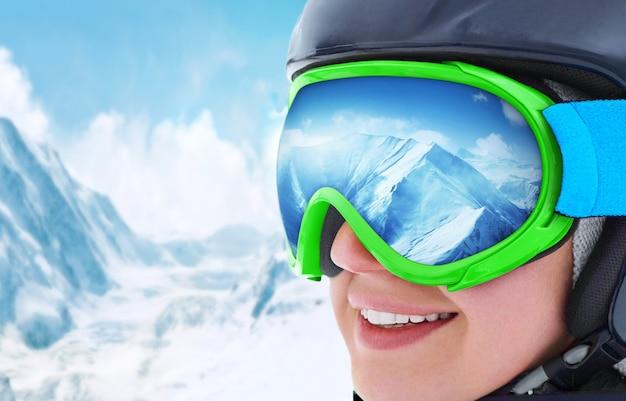 Snowboarden. porträt des jungen snowboarder-mädchens im skigebiet. bergkette spiegelt sich in der skimaske wider