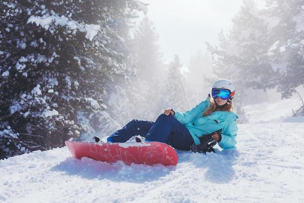 Snowboarder am hang an einem sonnigen morgen. mädchen im kleidungssnowboarder.