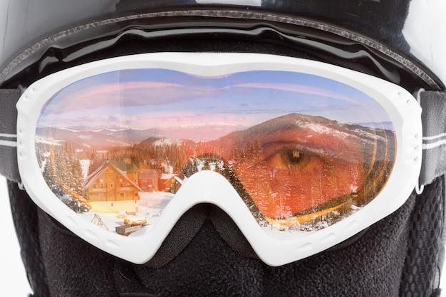 Snowboarder, der die berglandschaft durch eine brille betrachtet