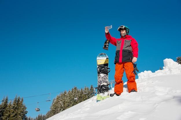Snowboarder, der intelligentes telefon in den bergen verwendet