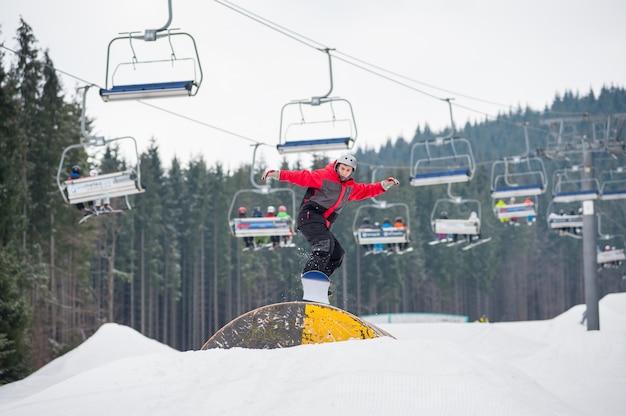 Snowboarder, der über eine hürde am wintertag fliegt