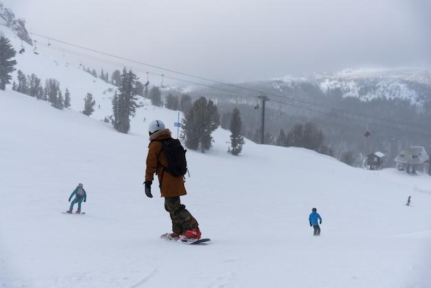 Snowboarder genießen abends skifahren in den bergen am hang im winterskigebiet mammoth lakes