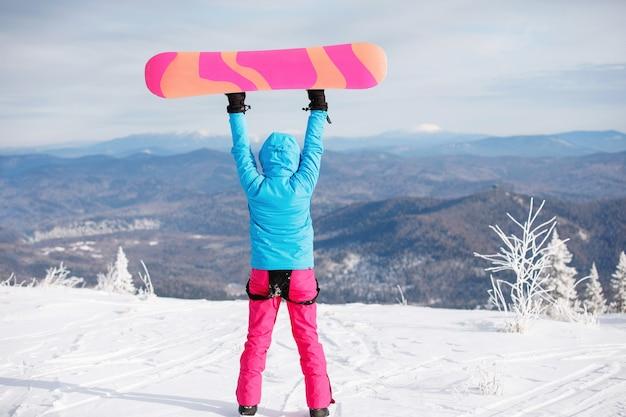 Snowboarder hält das board hoch. blaue jacke mit kapuze, strickmütze, skibrille. gesunder lebensstil
