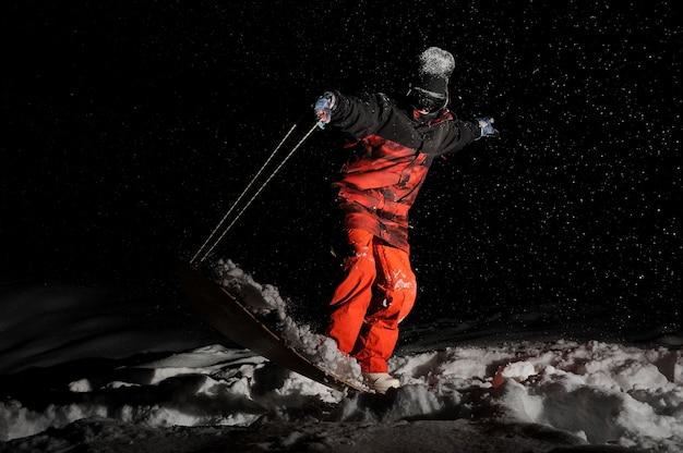 Snowboarder kleidete in der orange sportkleidung an, die auf dem brett balanciert