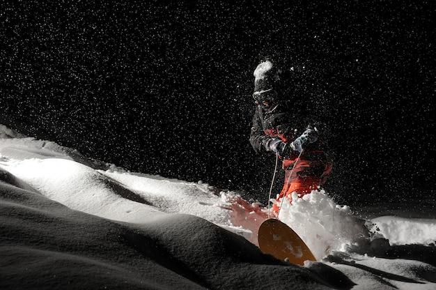 Snowboarder kleidete in der orange sportkleidung an, die mit dem snowboard reitet
