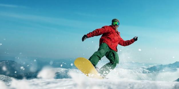 Snowboarder macht einen sprung, vorderansicht, sportler in aktion. aktiver wintersport, extremer lebensstil. snowboarden in bergen, blauer himmel