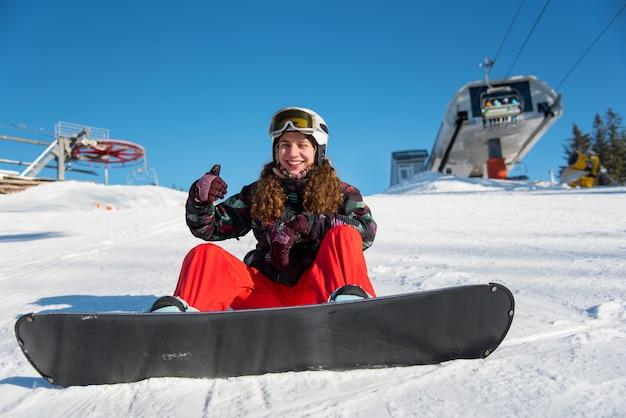 Snowboarder-mädchen, das im schnee nahe einem skilift gegen einen blauen himmel sitzt und daumen hoch gesten der guten klasse zeigt